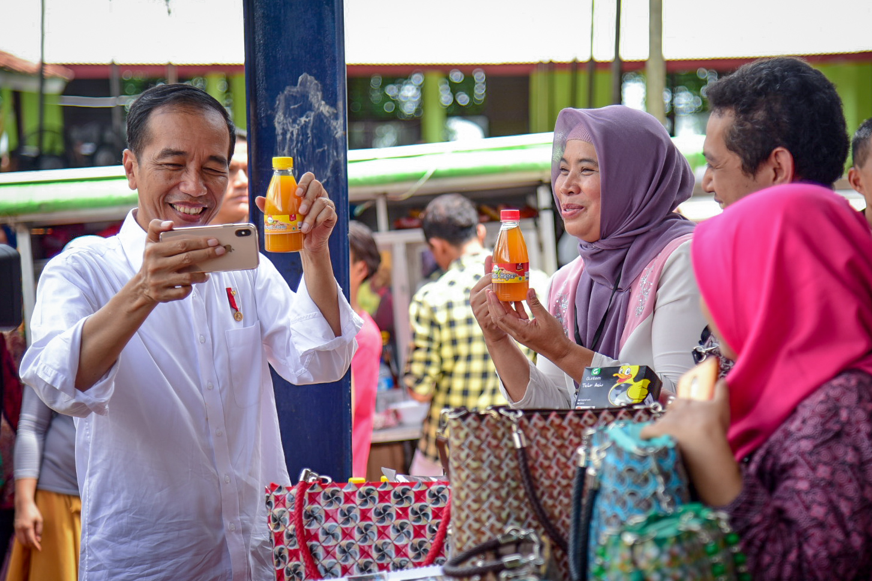 Presiden Jokowi berswafoto dengan produk salah satu peserta program Mekaar, di Muara Gembong, Bekasi, Jabar, Rabu (30/1) siang. (Foto: AGUNG/Humas)