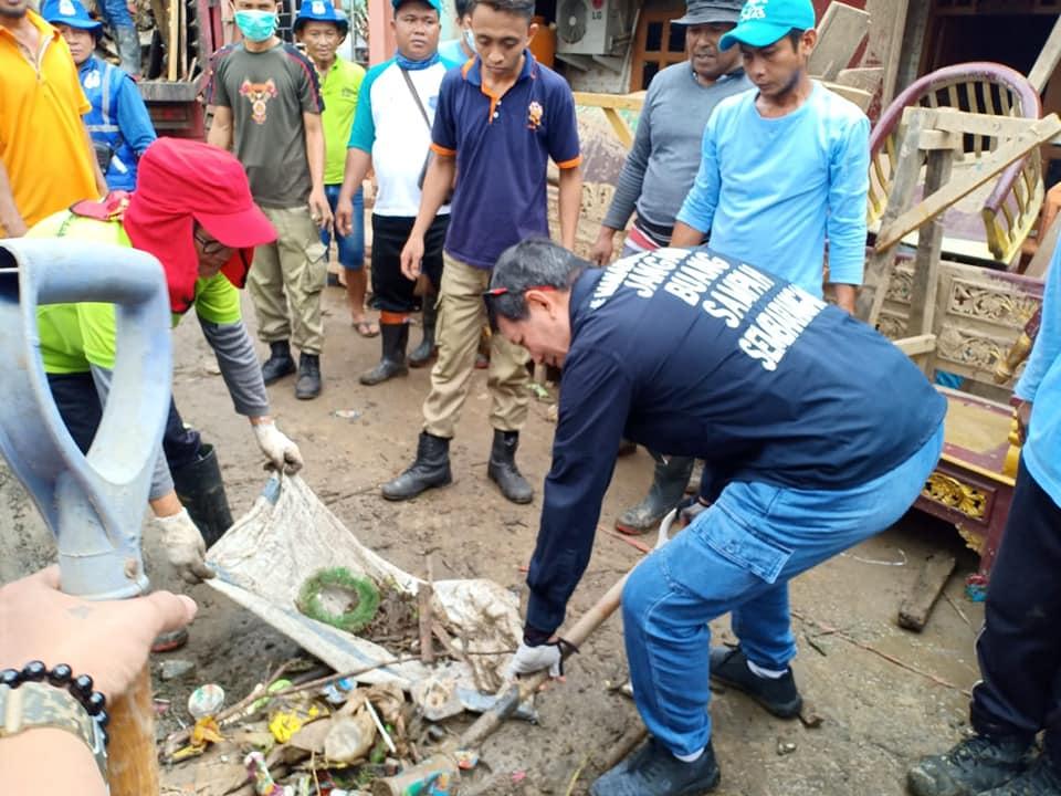 Dengan memegang sekop Walikota Vicky Lumentut membantu mengangkat sampah bercampur lumpur yang berserakan di jalan
